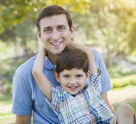 Smiling father sitting with young son